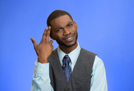 bonkers: Closeup portrait rude, difficult, angry young executive businessman gesturing with fingers against temple, are you crazy? Isolated blue background. Negative human emotion, facial expression, feelings