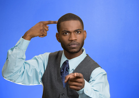 bonkers: Closeup portrait rude, difficult angry young executive businessman gesturing with fingers against temple are you crazy? Isolated blue color background. Negative human emotion facial expression feeling