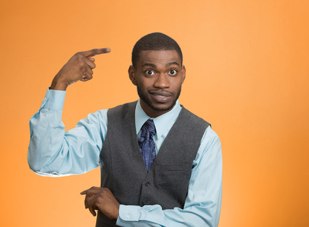 Closeup portrait rude difficult angry young executive businessman gesturing with finger against temple are you crazy? Isolated orange color background. Negative human emotion facial expression feeling Stock Photo
