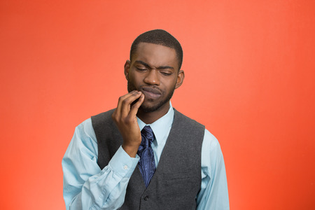 Closeup portrait handsome sad young executive man, student, worker touching face having bad pain, tooth ache, isolated red background. Negative human emotions, facial expressions, feeling reaction photo
