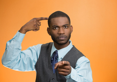bonkers: Closeup portrait rude difficult angry young executive businessman gesturing with finger against temple are you crazy? Isolated orange color background. Negative human emotion facial expression feeling Stock Photo