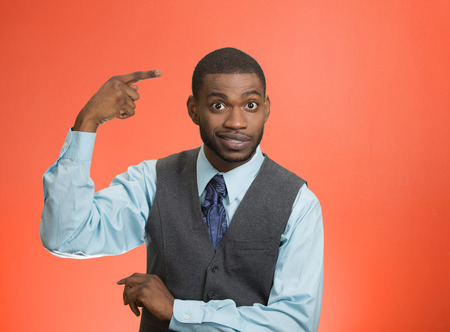 Closeup portrait rude, difficult, angry young executive businessman gesturing with fingers against temple, are you crazy? Isolated red background. Negative human emotion, facial expression, feelings Stock Photo