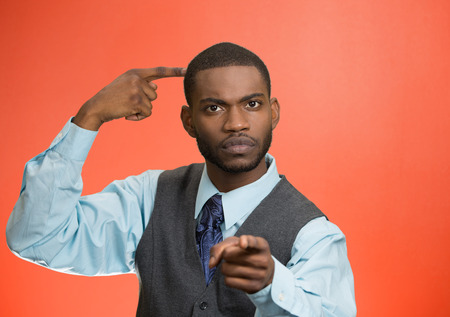 bonkers: Closeup portrait rude, difficult, angry young executive businessman gesturing with fingers against temple, are you crazy? Isolated red background. Negative human emotion, facial expression, feelings Stock Photo