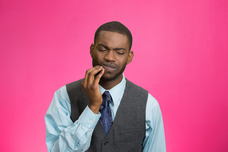 pain killers: Closeup portrait handsome sad young executive man, student, worker touching face having bad pain, tooth ache, isolated pink background. Negative human emotions, facial expressions, feeling reaction