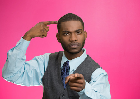 bonkers: Closeup portrait rude, difficult, angry young executive businessman gesturing with fingers against temple, are you crazy? Isolated pink background. Negative human emotion, facial expression, feelings Stock Photo
