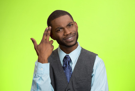 bonkers: Closeup portrait rude, difficult, angry young executive businessman gesturing with fingers against temple, are you crazy? Isolated green background. Negative human emotion, facial expression, feelings Stock Photo