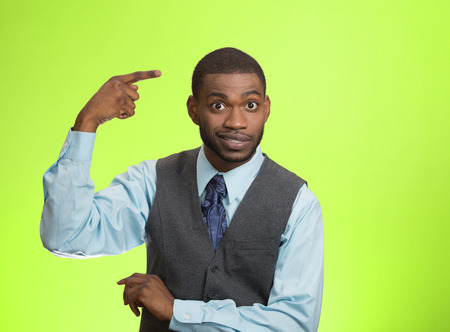 Closeup portrait rude, difficult, angry young executive businessman gesturing with fingers against temple, are you crazy? Isolated green background. Negative human emotion, facial expression, feelings Stock Photo