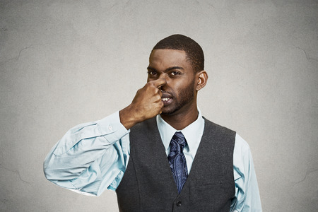 stinks: Closeup portrait young executive man, disgust on face, pinches his nose, something stinks, bad smell, situation isolated grey background. Negative emotion facial expression, perception body language Stock Photo