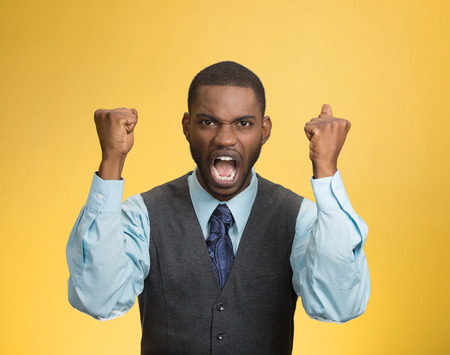 pissed: Closeup portrait bitter mad, displeased pissed off, angry grumpy corporate man, open mouth, hands in air, screaming, yelling isolated yellow background. Negative human emotion facial expression feeling Stock Photo