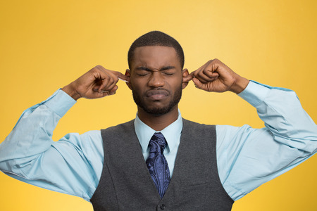 fedup: Closeup portrait unhappy, annoyed man plugging closing ears with fingers, disgusted ignoring something not wanting to hear someone side story, isolated yellow background. Human emotion body language
