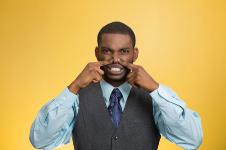 fart: Closeup portrait young executive man, disgust on face, pinches his nose, something stinks, bad smell, situation isolated yellow background. Negative emotion facial expression, perception body language