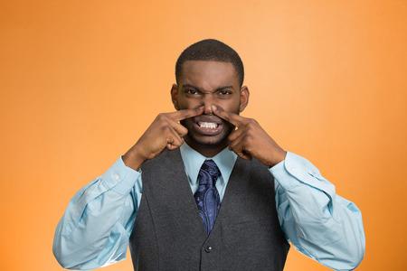 expresion corporal: Retrato del primer ejecutivo hombre joven, disgusto en el rostro, pellizca la nariz, algo huele mal, mal olor, situación aislada de fondo naranja. La emoción negativa la expresión facial, el lenguaje corporal percepción