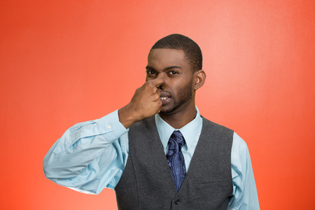stinks: Closeup portrait young executive man, disgust on face, pinches his nose, something stinks, bad smell, situation isolated red background. Negative emotion facial expression, perception body language