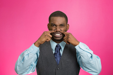 pinches: Closeup portrait young executive man, disgust on face, pinches his nose, something stinks, bad smell, situation isolated pink background. Negative emotion facial expression, perception body language