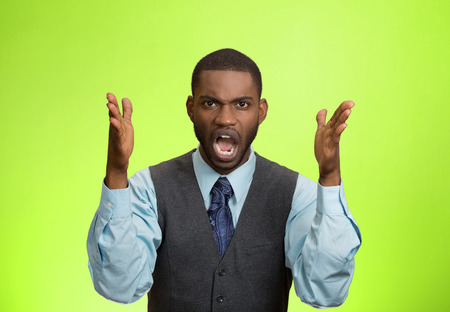 aggravated: Closeup portrait bitter mad, displeased pissed off, angry grumpy corporate man, open mouth, hands in air, screaming, yelling isolated green background. Negative human emotion facial expression feeling Stock Photo