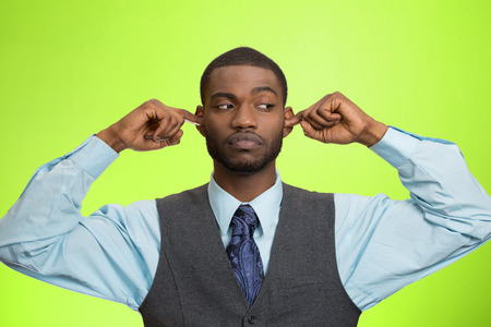 fedup: Closeup portrait unhappy, annoyed man plugging closing ears with fingers, disgusted ignoring something not wanting to hear someone side story, isolated green background. Human emotion body language Stock Photo