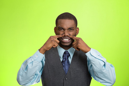 stinks: Closeup portrait young executive man, disgust on face, pinches his nose, something stinks, bad smell, situation isolated green background. Negative emotion facial expression, perception body language