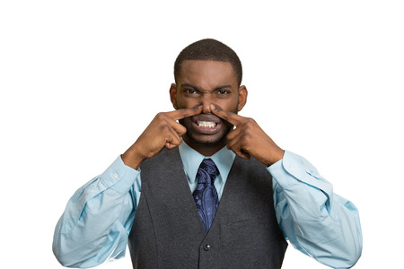 intolerable: Closeup portrait young executive man, disgust on face, pinches his nose, something stinks, bad smell, situation isolated white background. Negative emotion facial expression, perception body language Stock Photo