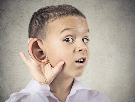 big ear: Closeup portrait, headshot boy, little man overhearing something, hand to big ear gesture, very curious, isolated grey, black background  Human face expression, emotion, body language, life perception