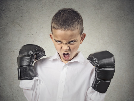 Closeup portrait headshot pissed off, Aggressive Child wearing Boxing Gloves, screaming, isolated on grey background  Negative human emotions, Face Expression, body language, life perception, attitude photo