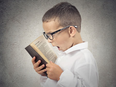 Closeup side view profile portrait, Headshot funny looking, Shocked Boy Reading story, Book, isolated grey background  Human face expressions, emotions, reaction, body language, perception  photo