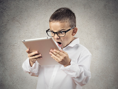 Closeup portrait child, shocked, surprised, funny looking boy with glasses using, holding laptop, pad computer isolated grey, black background  Human face expressions, emotions, reaction body language