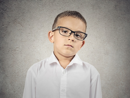 annoy: Closeup portrait skeptical boy with glasses looking carefully suspicious, skepticism on face, disapproval isolated grey background  Human emotion, facial expression, feeling attitude, body language Stock Photo