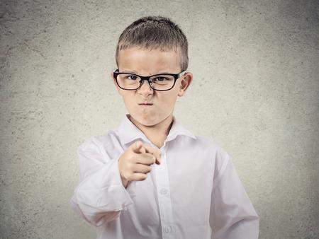 Close-up portret boos, gek kind vermomd als baas, executive zakenman, wijzende vinger op iemand, misnoegd, geïsoleerde grijze achtergrond Menselijk gezicht uitdrukkingen, emoties, gevoelens, lichaamstaal Stockfoto