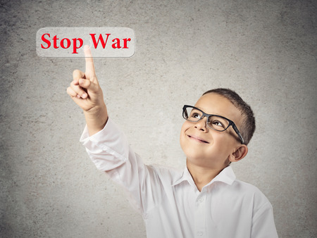 Closeup portrait happy, smiling child touching red button, icon stop war on touchscreen display, isolated grey background  Positive face expression, emotions life perception  Politics, Peace concept photo