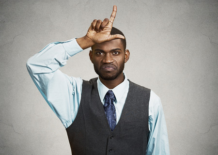 bother: Closeup portrait angry mad young Unhappy Man, student displaying Loser Sign on forehead, pointing at you with disgust, isolated grey background. Negative human emotion, facial expression Body Language