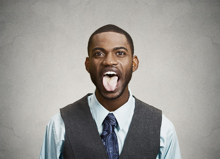 cause: Closeup portrait funny, annoyed, young business man, employee sticking out his tongue, isolated grey background. Human face expressions, emotions, attitude, body language, life perception, reaction