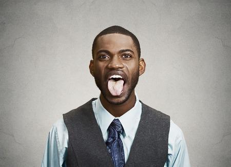 sacar la lengua: Primer retrato divertido, molesto, joven hombre de negocios, empleado sacando la lengua, aislado fondo gris. Expresiones faciales humanas, emociones, actitud, lenguaje corporal, la percepción vida, reacción Foto de archivo
