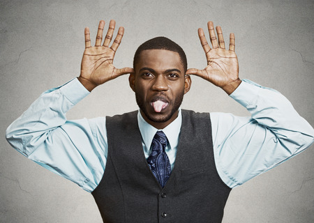 ridiculous: Closeup portrait young angry executive man, sticking out tongue at you, camera gesture, thumbs hands on temple, isolated grey background. Negative human emotions, facial expressions, feeling, attitude Stock Photo