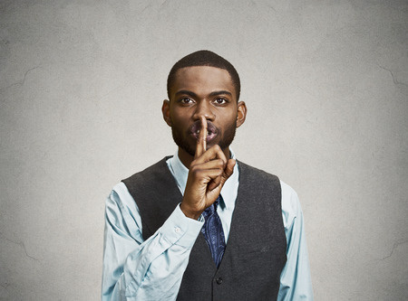 Closeup portrait young serious businessman placing finger on lips saying, shhh, be quiet, silence, isolated grey background. Facial expression, human emotions, sign, symbol, body language, perception Stock Photo