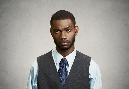 lenguaje corporal: Primer retrato, Headshot Deprimido joven hombre, aislado fondo de la pared gris. Las emociones negativas humanos, las expresiones faciales, el lenguaje corporal, percepción de la vida, sentimientos. Concepto de salud mental