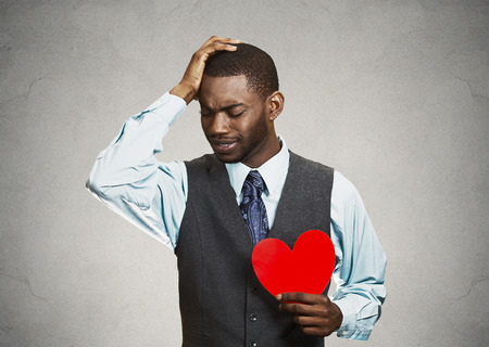 relationship breakup: Closeup portrait young sad confused corporate man, holding red heart in his hands, about to cry, looking up isolated grey, black background. Negative human emotion facial expression feelings, attitude Stock Photo