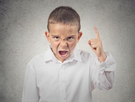ni�os malos: Retrato del primer ni�o enojado, Boy Screaming dedo apuntando hacia arriba, exigiendo justicia aisladas fondo de la pared gris emociones negativas humanos, las expresiones faciales, el lenguaje corporal, la actitud, la percepci�n