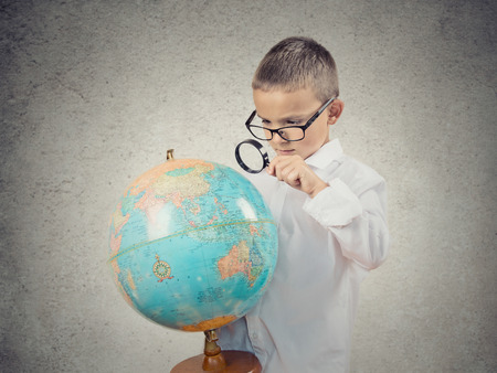 Closeup portrait curious child holding earth globe map in his hand, looking through magnifying loupe, picking his next destination isolated grey wall background  Human facial expression Travel concept photo