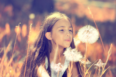Outdoor closeup portrait of a beautiful, happy young Girl Blowing Dandelion flower on a sunny summer day  Life Leisure, vacation, travel concept  Positive facial expressions, emotions, feelings photo