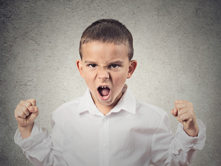 Closeup Portrait Angry child, Boy Screaming fists up in air, demanding justice, his rights isolated grey wall background. Negative human Emotion, Facial Expression, body language, attitude, perception photo