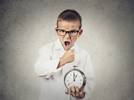 hurry up: Closeup portrait, Angry, Mad, pissed off Child, Boy, playing boss manager, Screaming, about to smash alarm clock with fist, isolated grey wall background. Negative human emotions, facial expressions