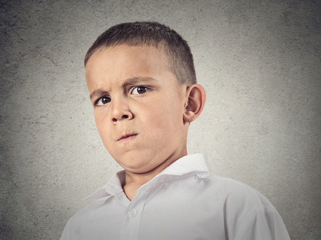 skepticism: Closeup up portrait, headshot suspicious, cautions child, boy looking at you with disbelief, skepticism, isolated grey wall background. Human facial expressions, emotions, body language, perception Stock Photo