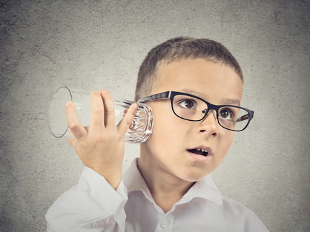secret information: Closeup portrait, headshot curious nosy child using a glass as telephone listening to conversation, gossip, isolated grey wall background. Human face expressions, emotions, feelings, life perception