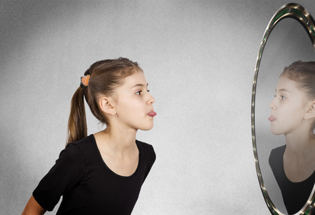 self conceit: Closeup side view profile portrait child, girl sticking her tongue out looking in the mirror, isolated grey wall background. Human facial expressions, emotions, feelings, life perception body language