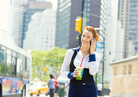 uptown: Business woman on smart phone in New York City, Manhattan walking on a street holding  cup of juice smiling. Young professional female businesswoman in her 20s. Positive facial expressions, emotions Stock Photo