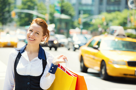 Shopping woman in New York City. Beautiful happy summer shopper holding shopping bags walking outside smiling with yellow taxi cab in background. Positive emotions. Caucasian model on Manhattan, USA.