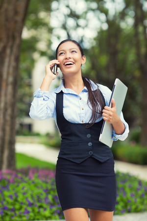 sidewalk talk: Portrait young Businesswoman on cellphone running while talking on smart phone, holding laptop  Happy, smiling mixed race beautiful business woman busy  Positive facial expressions, emotions, feeling Stock Photo