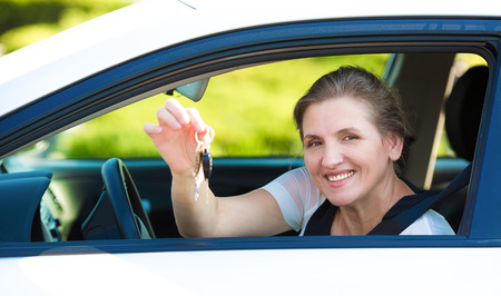 car lot: Closeup portrait happy, smiling, attractive woman, buyer sitting in her new white car showing keys isolated outdoors street dealership lot background.  Personal transportation, auto purchase concept
