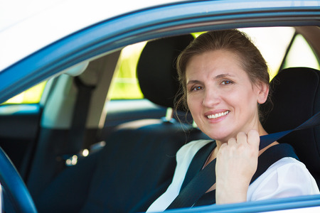 mother in law: Closeup portrait beautiful, smiling, happy, attractive woman pulling on seatbelt inside white car.  Driving safety, buckle up to prevent traffic death accidents concept  Save life  Face expression Stock Photo