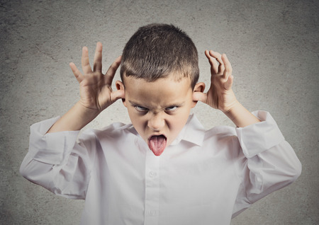 spurn: Closeup portrait angry young Unhappy boy, young student Mocking teasing, taunting other children isolated grey wall background. Negative human emotions, facial expressions, Body Language, attitude